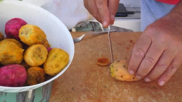 Az időeltolódás tüskés körtét hámoz. Egy késsel elvágják a tüskés körte külső rétegét, hogy az édes gyümölcsöt megegyék. Gyümölcs a tányéron, fogyasztásra kész.