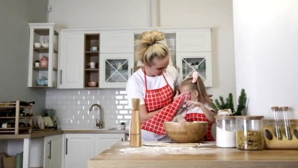 Mladá blondýna matka s malou dcerou v zástěrách se zabývá vařením u stolu v kuchyni.