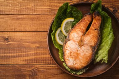 Baked trout steak in pottery with salad and slices of lemon