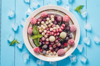 Frozen berries in the plate on wooden table, top view