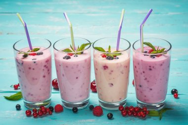 Four glasses of various fresh berries smoothies