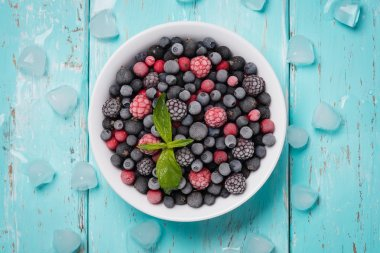 Frozen berries on a turquoise background, top view