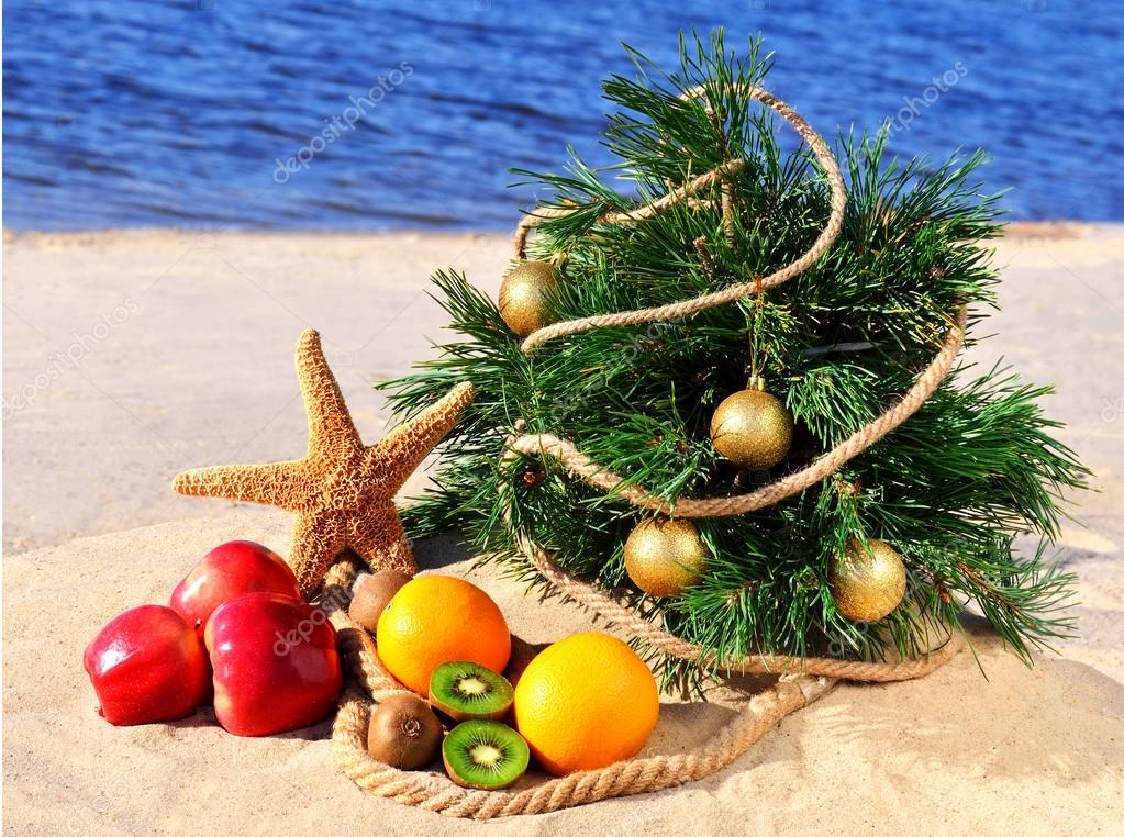 Festive christmas tree with ripe fruits and starfish on the sand