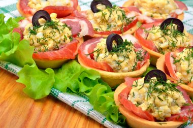 Holiday tartlets stuffed with eggs, ham, olives and green lettuc