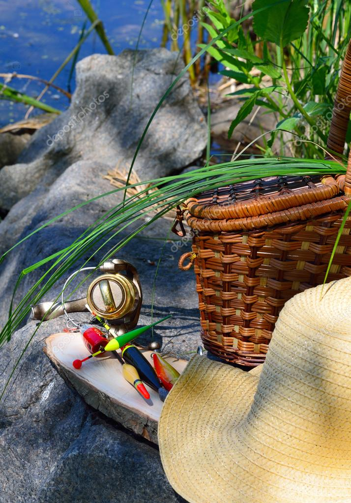 fishing tackle with wicker basket and hat on the background