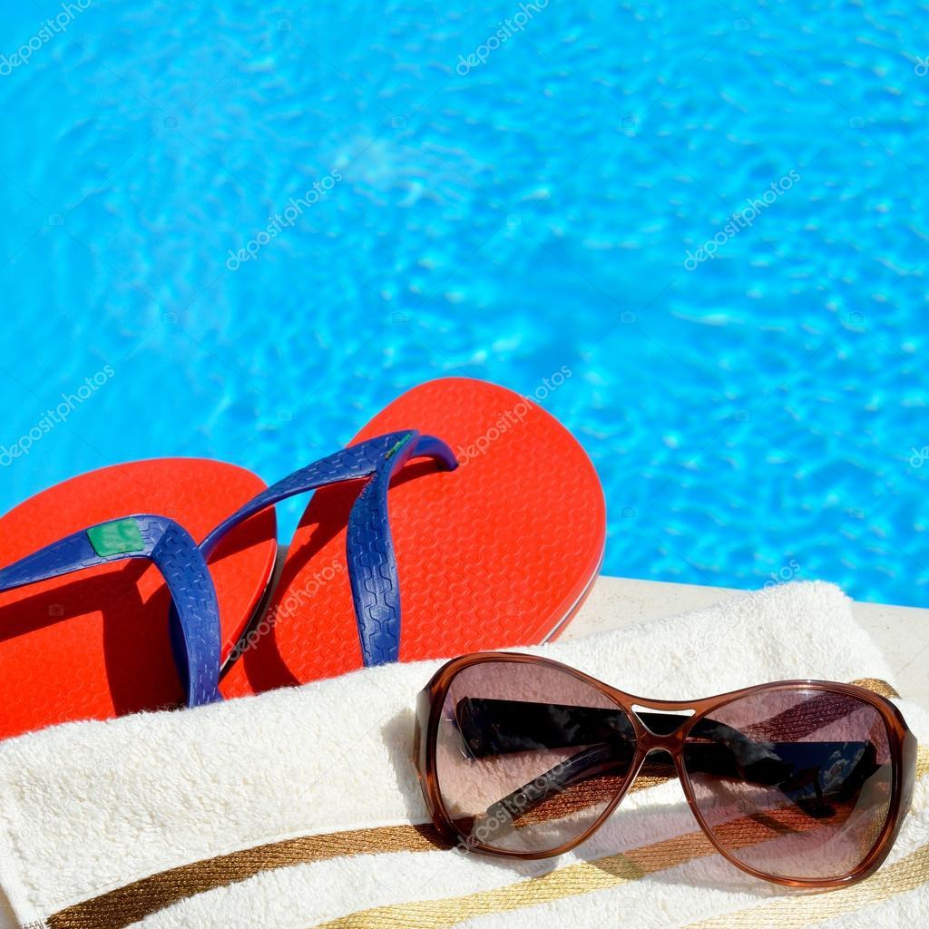 953df5e89a30e Güneş gözlüğü, plaj havlusu ve havuz kenarında parmak arası terlik– stok  imaj