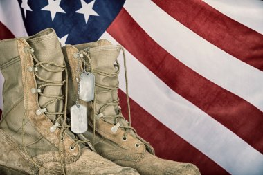 Old combat boots and dog tags with American flag