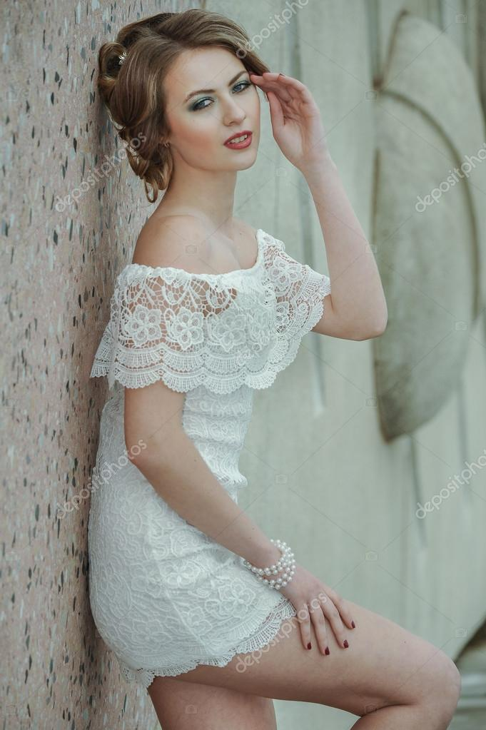 Beautiful stylish girl posing in short white dress against stone ...