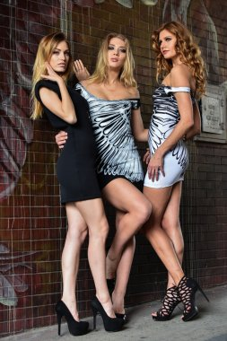 Fashion outdoor photo of three beautiful models