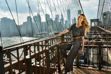 Young smiling model with long blonde hair posing at the bridge
