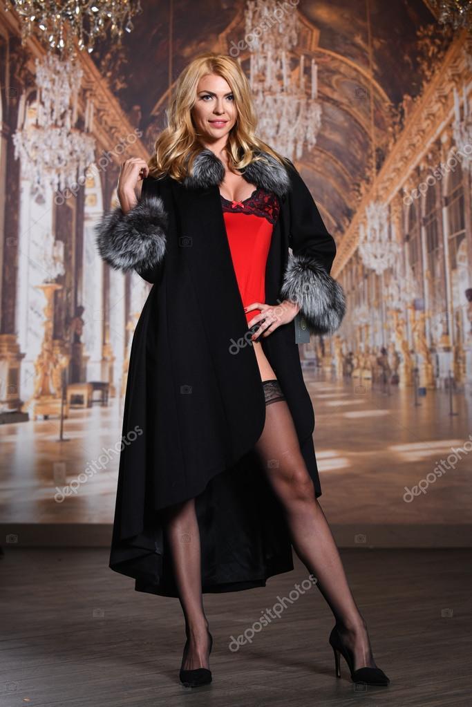 6d716bcb7e9b40 Мода володарки спокусливі світлим волоссям в елегантному шуба, червоний  сексуальне жіноча білизна і панчохи позують тлі шпалер. — Фото від  fashionstock