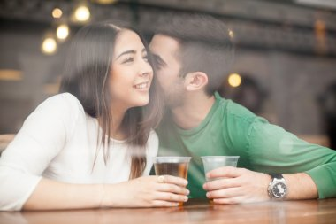 Guy drinking beer at a bar and whispering