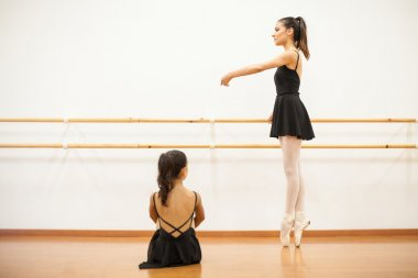 girl sitting and watching a real ballet dancer