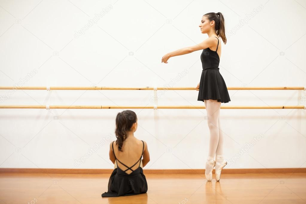 Girl sitting and watching a real ballet dancer — Stock Photo