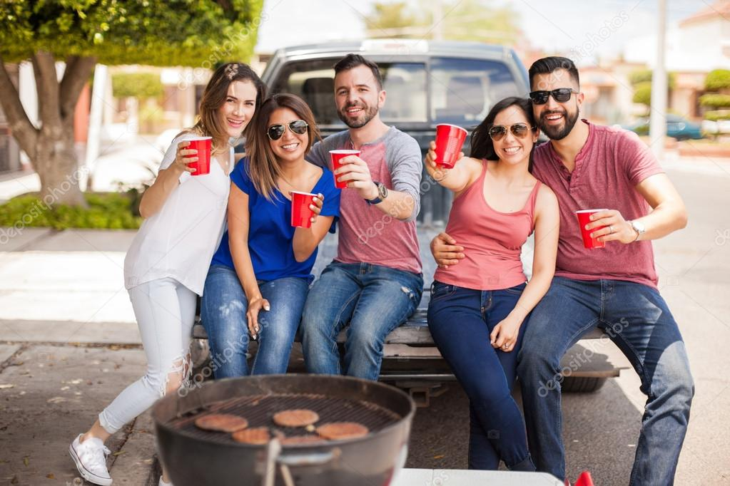 Group of friends tailgating and grilling burgers