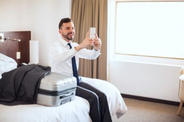 Good looking young businessman sharing the details of his business trip on social media by taking a selfie with his smartphone stock vector