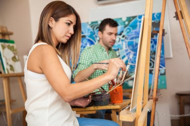 Profile view of a couple of adults working on a painting at an art school stock vector