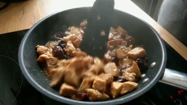 Kousky masa a švestek se vaří v pánvi