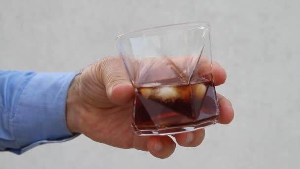 Mužská ruka krouží sklenicí whisky a kostky ledu