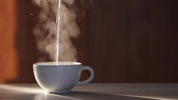 Pouring hot black tea into a white cup on a wooden table. Steam coming from the cup.