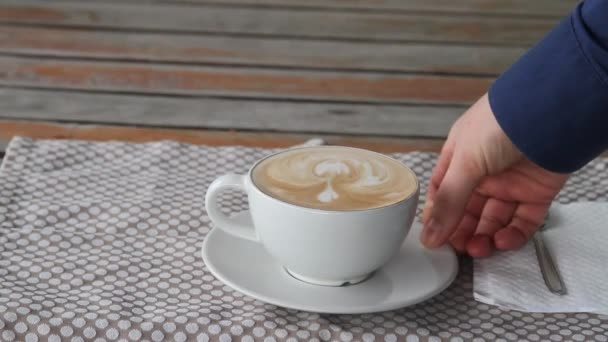 Close-up of person hands stirring coffee with spoon in a white cup