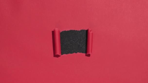 Risse bei der Öffnung von rotem Papier, um schwarzen Kopierraum aufzudecken