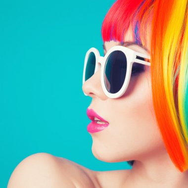 Beautiful woman wearing colorful wig and white sunglasses against blue background stock vector