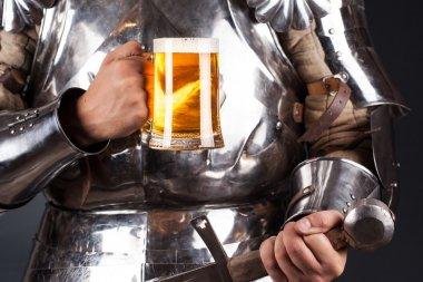 Knight holding mug of beer and two-handed sword