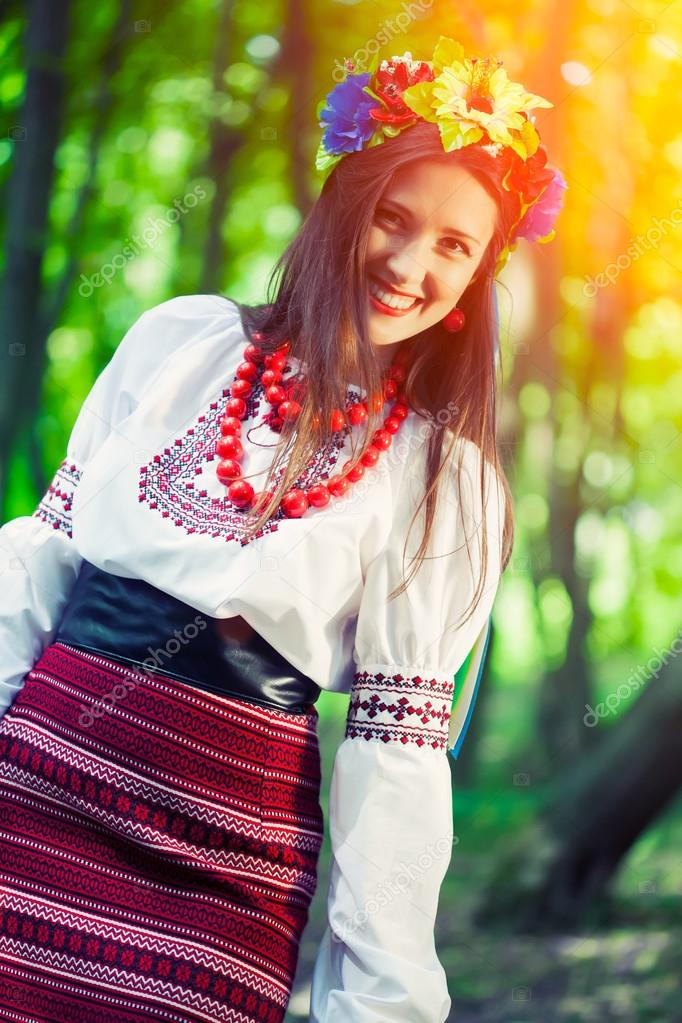 Woman wearing national ukrainian clothes posing in forest