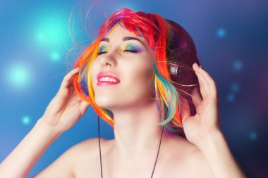 Beautiful woman wearing colorful wig and headphones against blue background stock vector