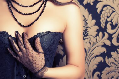 Woman wearing black corset and pearls