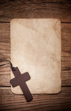 Wooden cross on paper isolated on brown  background stock vector