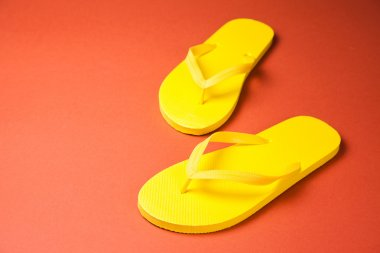 Yellow flip-flops on a red background