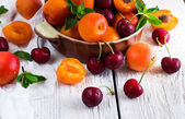 Ceramic bowl with organic ripe apricots and cherries