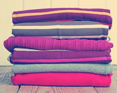 Stack of warm knitting clothing on a wooden table