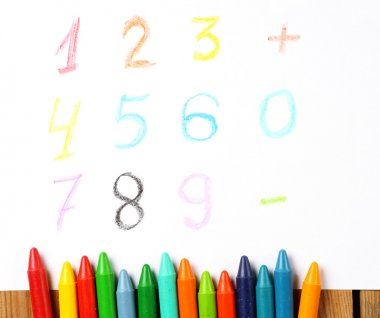Crayons lying on a paper with painted digit, number, sign