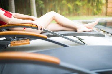 Elegant girl in swimsuit lying on sun lounger.