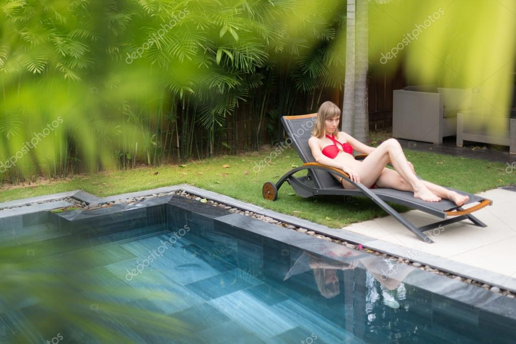 Woman Relaxing On Chaise Longue Near Pool Stock Photo 57770533