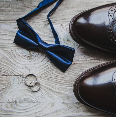 Close up of Wedding details, rings, grooms bow-tie and shoes