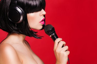 Beautiful singing woman with microphone. Singer. Karaoke song. on red background