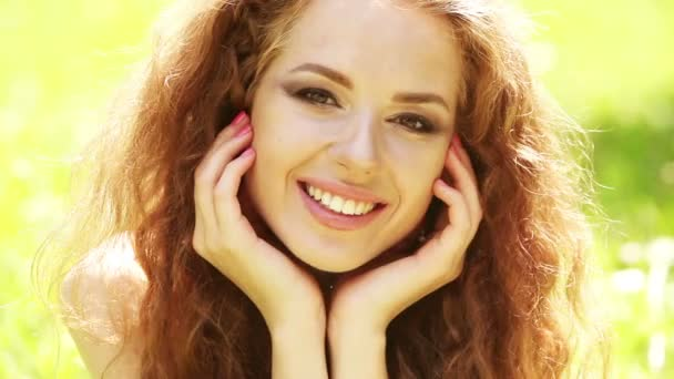 Beauty girl with healthy long curly hair outdoors. Happy smiling young woman falling down on the grass.