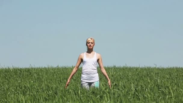 blonde woman doing yoga in a field