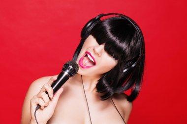 Karaoke woman listening to music on headphones enjoying a singing. Closeup portrait of beautiful girl with pink lips.