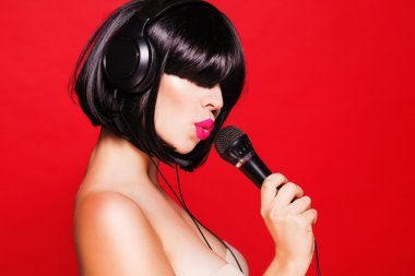 Woman with microphone listening to music on headphones enjoying a singing. Karaoke