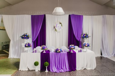 Head table for newlyweds at the wedding hall. Purple, violet tableware