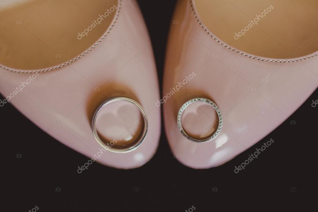 Two gold rings laying on white wedding bridal shoes