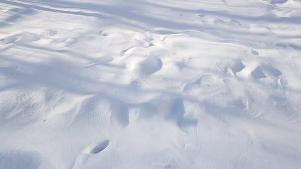 Pohled na sněhové závěje s nepravidelnostmi a vlnitým vzorem.