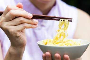 Woman eating noodle