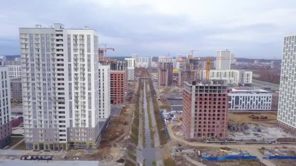 Ekaterinburg, Russia. Flight between buildings under construction over the river. New Construction Area - Akademicheskiy (Academic). 4K