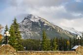 Sněhem pokryté pohoří Rundle se zasněženým lesem nad modrou oblohou a bílými mraky v zimním slunném dni. Banff National Park, Canadian Rockies.